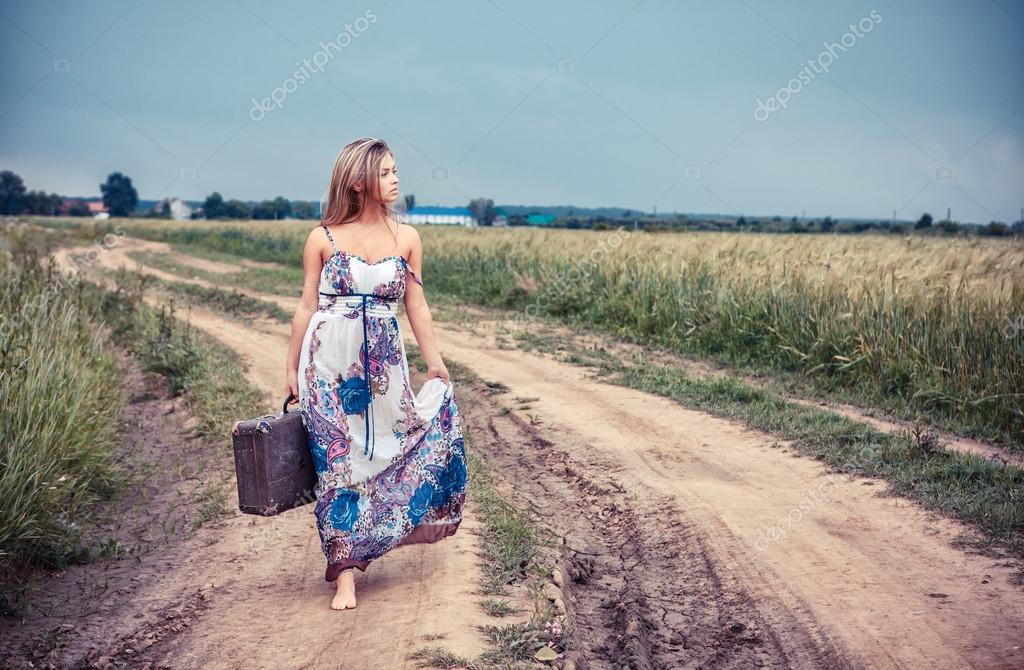 walking girl with old suitcase on the road