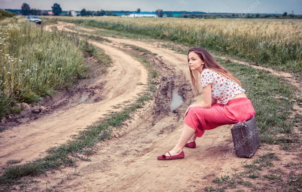 Beautiful girl waiting on a country road with old suitcase
