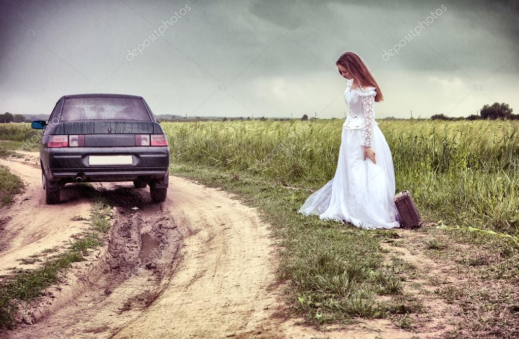 The thrown bride on the rural road with an old suitcase