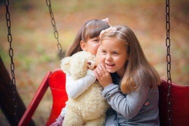 Girlfriends on swing in park