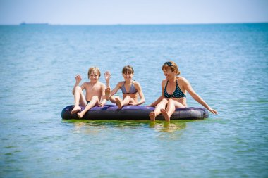 Family  on air bed on sea