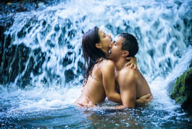 Couple hugging and kissing under waterfall stock vector