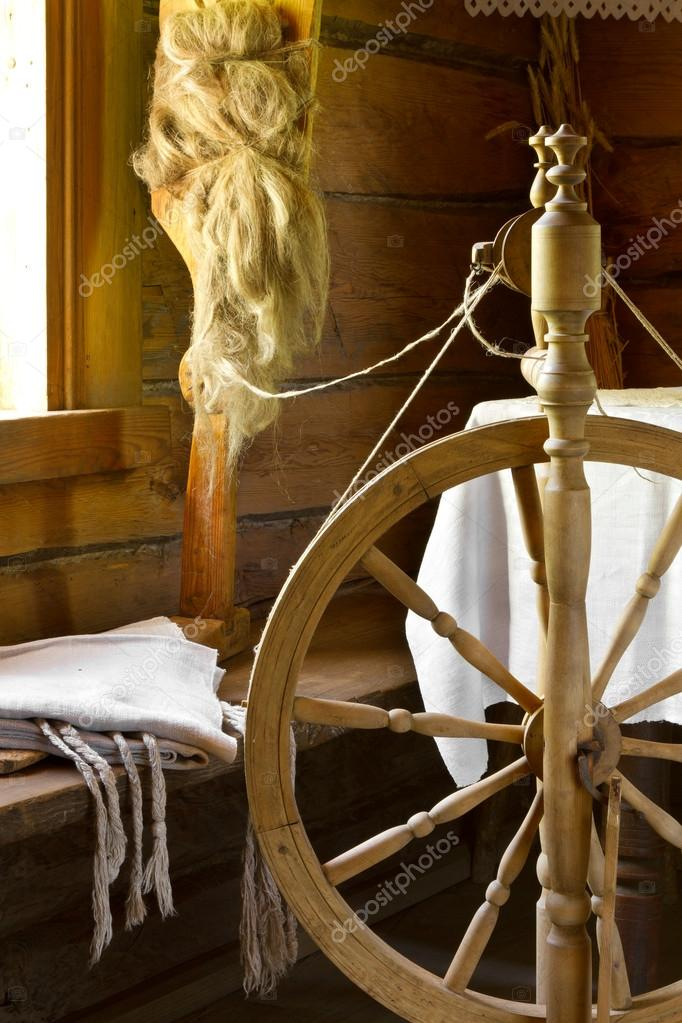 Vintage traditional spinning wheel, distaff with yarn in wooden home interior