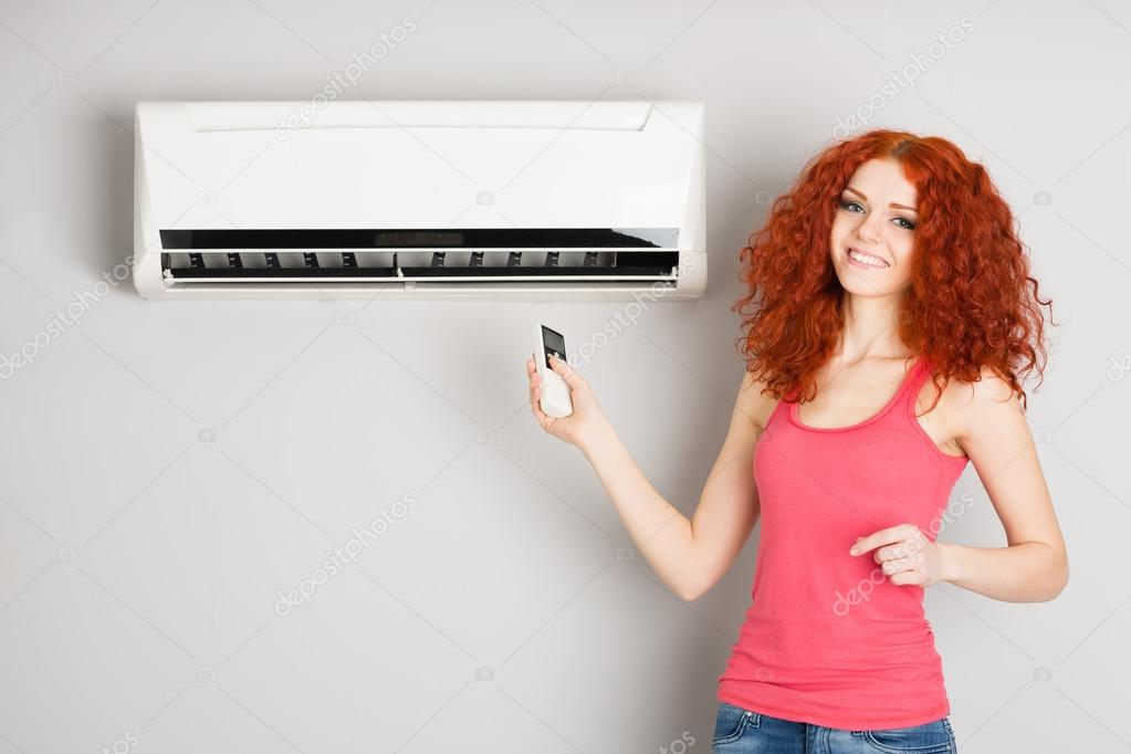 Smiling redhead girl holding a remote control air conditioner