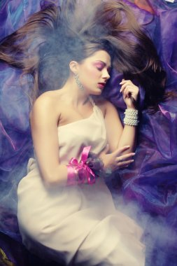 Beautiful woman lay on organza. Sleeping beauty.
