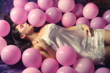 Sleeping woman lying on floor among balloons