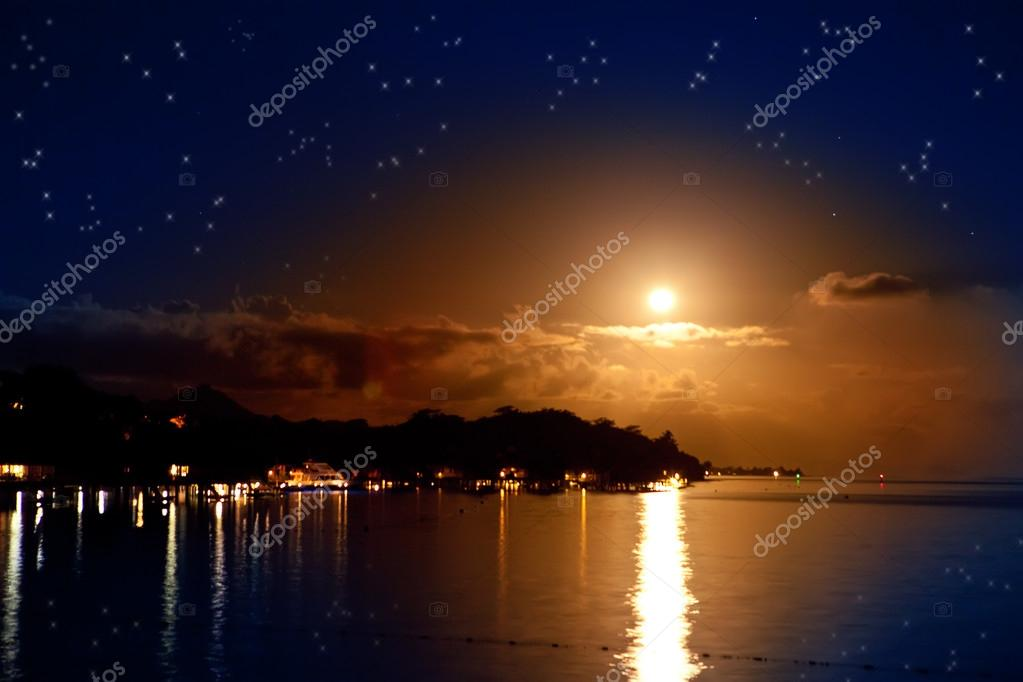 Night. The moon over the sea and reflection in water