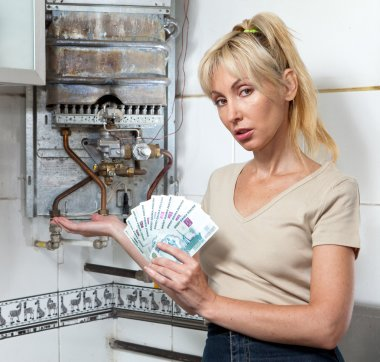 The sad woman the housewife counts up money for repair of a gas water heater
