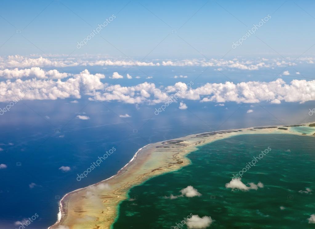 Polynesia. The atoll in ocean through clouds. Aerial view
