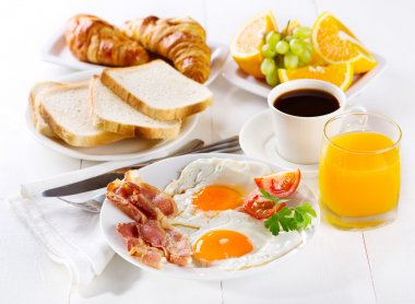 Breakfast with fried eggs, croissants, juice, coffee and fruits stock vector