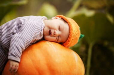 Baby sleeping on big pumpkin