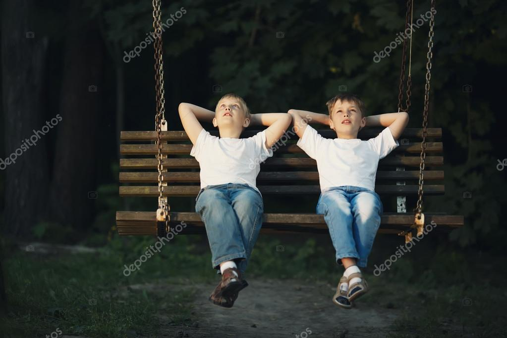 little boys riding on a swing