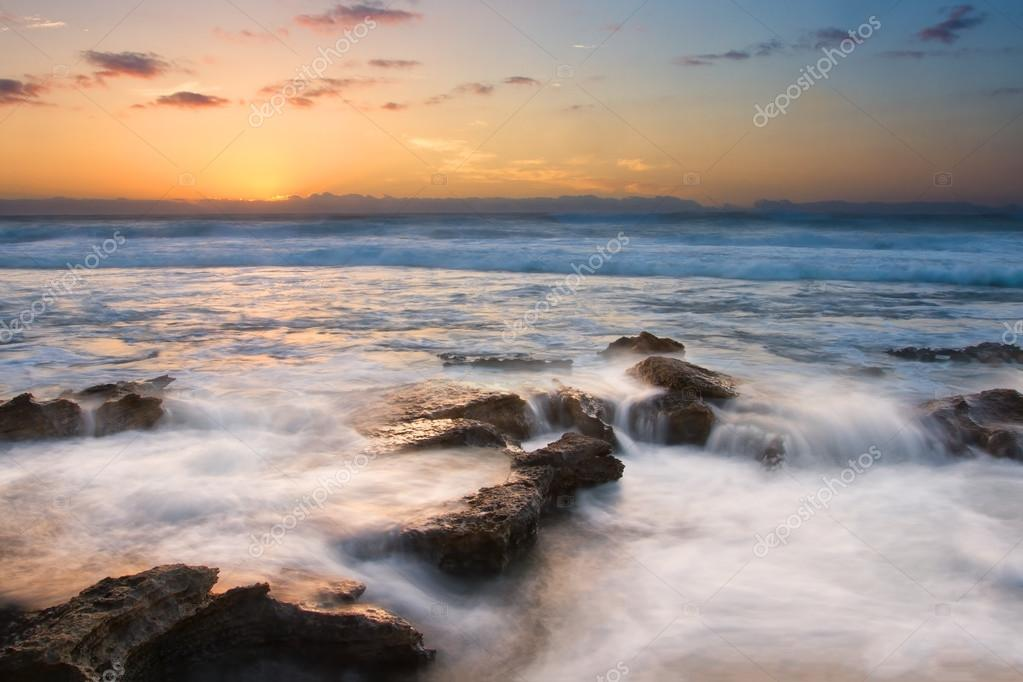 Фотообои Sunrise landscape of ocean with waves clouds and rocks