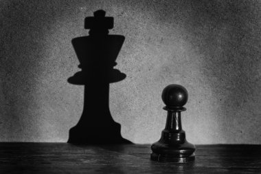 Chess pawn standing in a spotlight that make a shadow  actistic