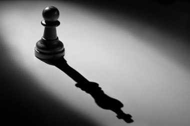 Chess pawn standing in a spotlight that make a shadow of king