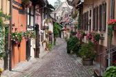 strada con case a graticcio medievali nel villaggio di eguisheim, lungo la famosa strada del vino in Alsazia, Francia