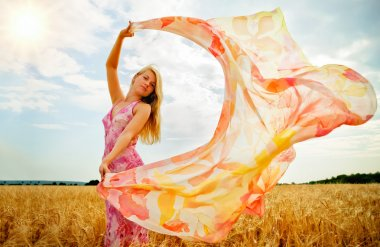 The young woman in the field holding scarf to wind.