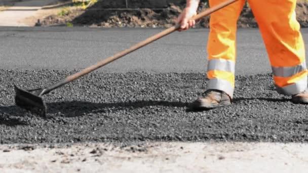 silniční stavební dělník vyrovnání asfaltu pomocí hrábě v zadní silniční válec procházející
