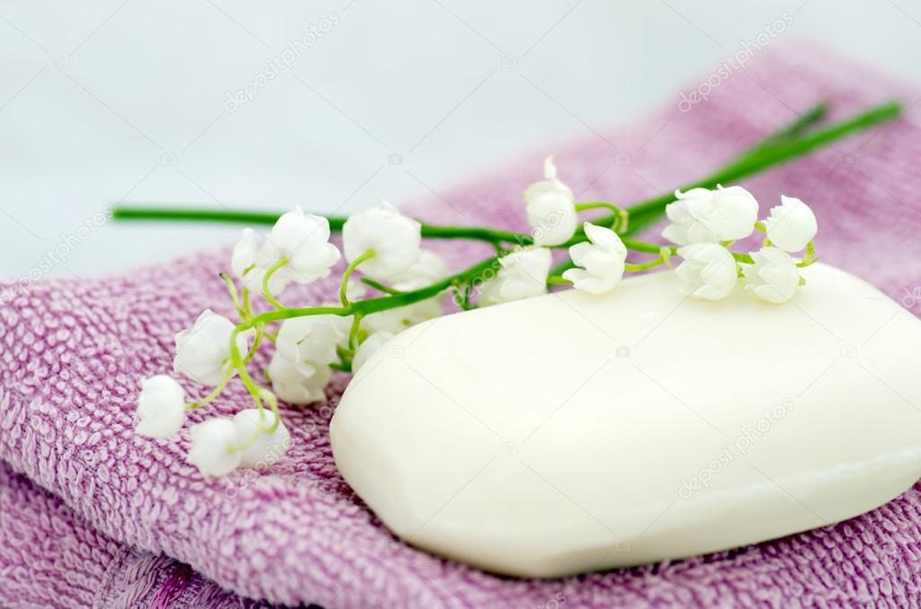 Spa setting of towels, soap and lilies of the valley