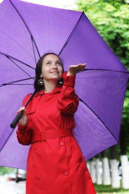 Woman with umbrella catching rain drops