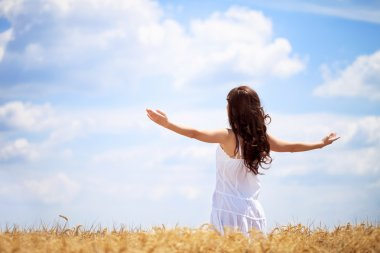Woman in wheat field enjoying