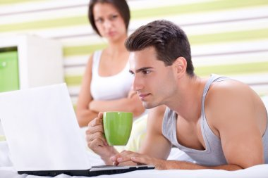 Couple with laptop in bed.