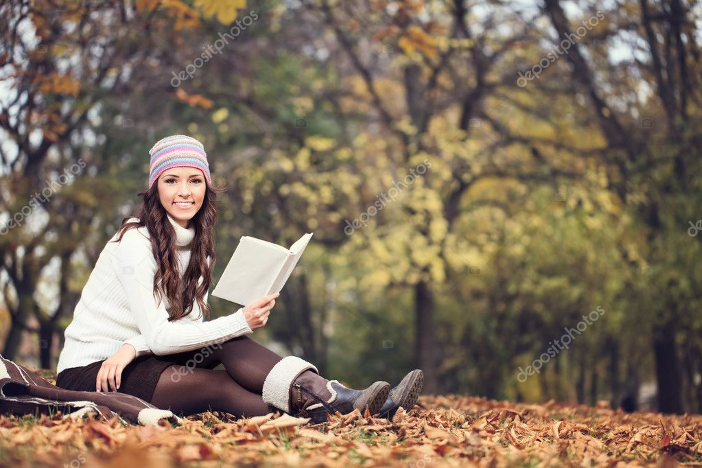 Woman with book in autumn park