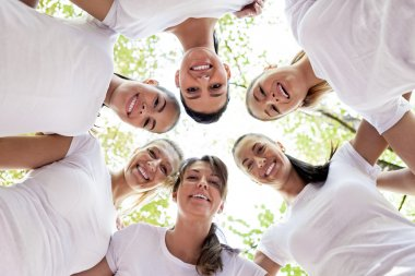 Group of women standing in the circle, smiling at the camera, low angle view. stock vector