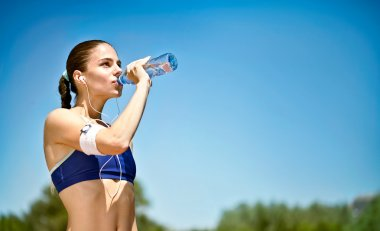 Woman athlete takes a break, she drinking water, out on a run on a hot day stock vector