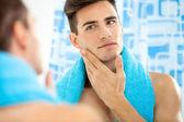 člověk dotýká obličeji po holení
