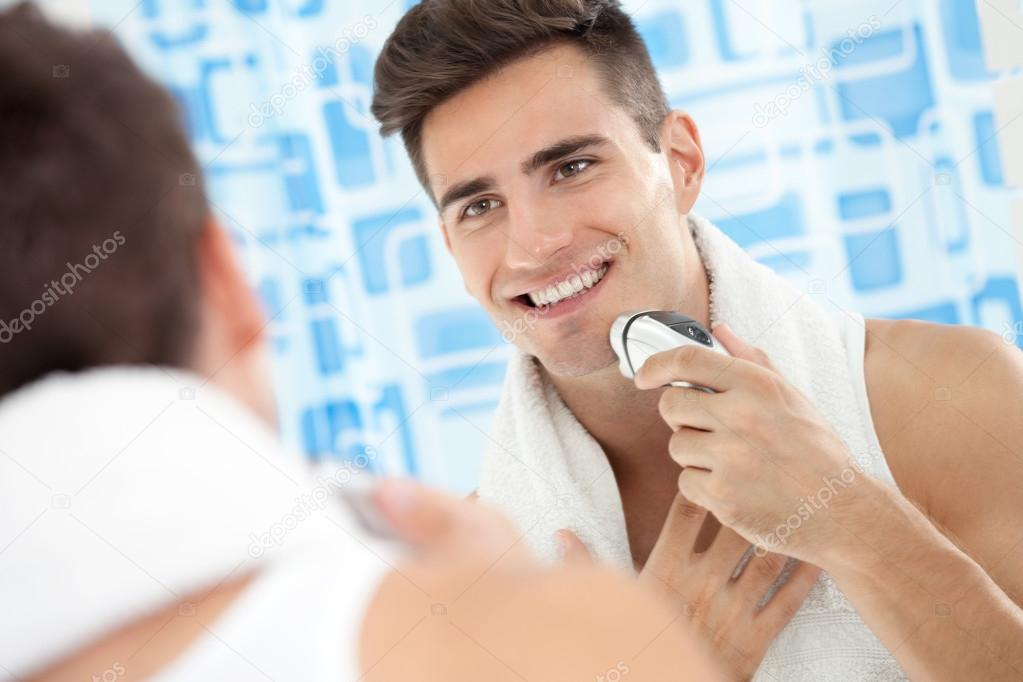 Smiling man using electric shaver