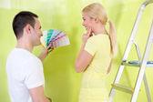 Fotografie Lächelndes Paar mit Farbmustern zum Malen