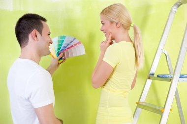 Smiling couple  with color samples to paint