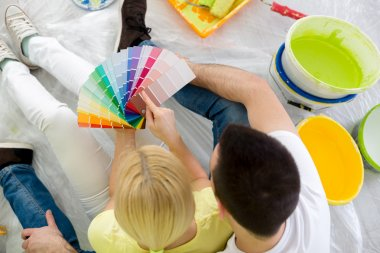 Couple sitting on floor and choosing color for painting