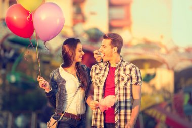 Love couple in amusement park with cotton candy