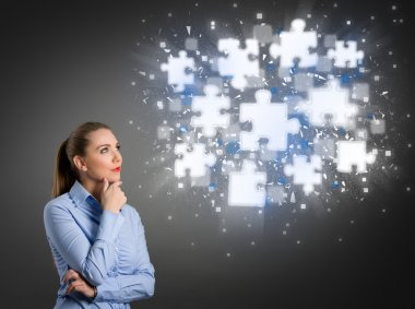 Thinking businesswoman looking at shining puzzle pieces