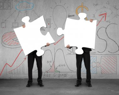 Two men assembling puzzles with business doodles background