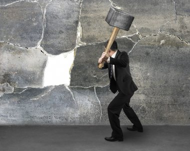 Businessman holding sedgehammer to crack wall