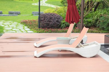 Wicker deck chair and table in the beautiful summer park with gr