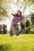 Fotografie Happy young woman jumping in park