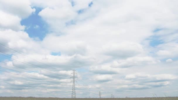 Clouds and blue sky behind an electricity pylon