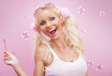 Portrait of young nice woman with soap bubbles on pink back