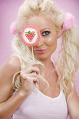 Portrait of young nice woman with lollypop on pink back