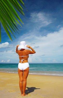 View of nice woman in white panama and bikini on tropical beach