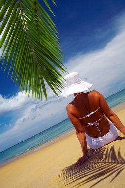 View of nice woman lounging on tropical beach in white panama and bikini