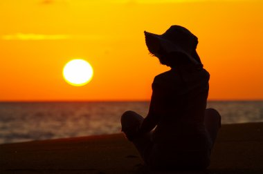 Silhouette of a woman on the beach during sunset