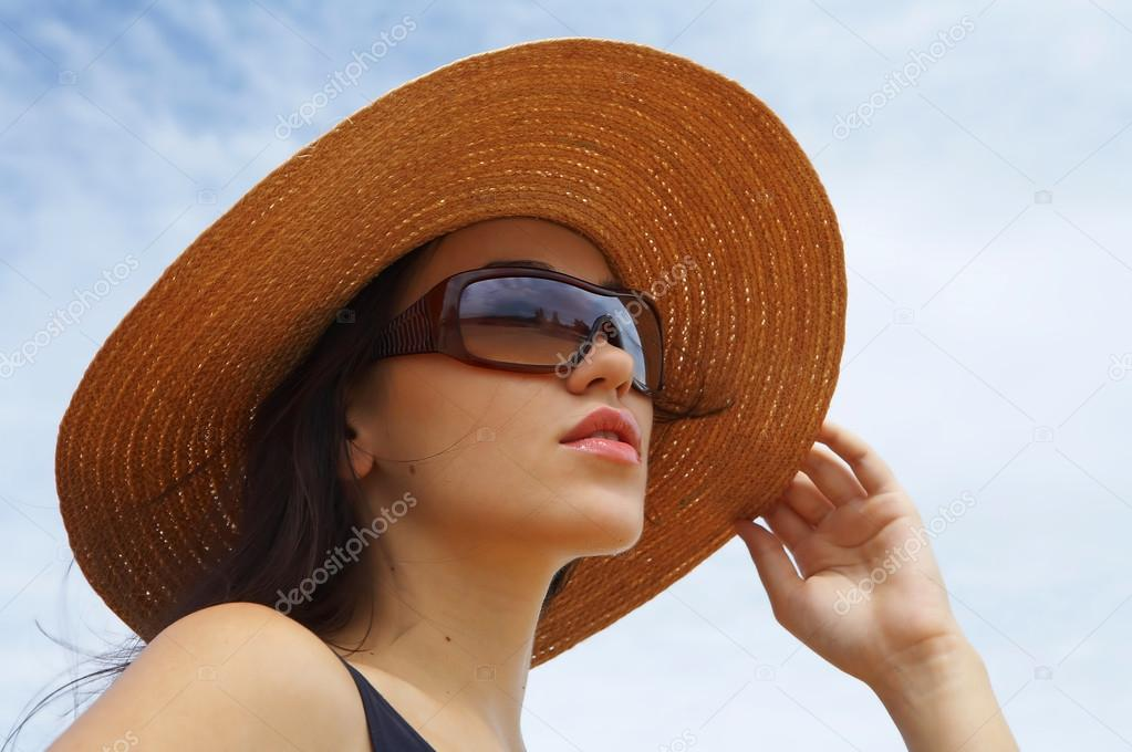 View of nice woman in black swimming wear holding her straw hat