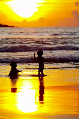 View of two kids bathing during nice colorful sunset