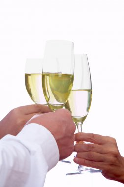 View of champagne flutes making a toast on white background