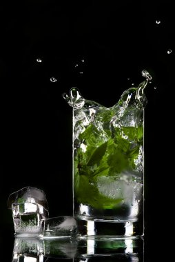 View of glass filled with green tea and ice cubes aside